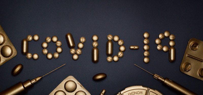 covid-19 written out in golden pills